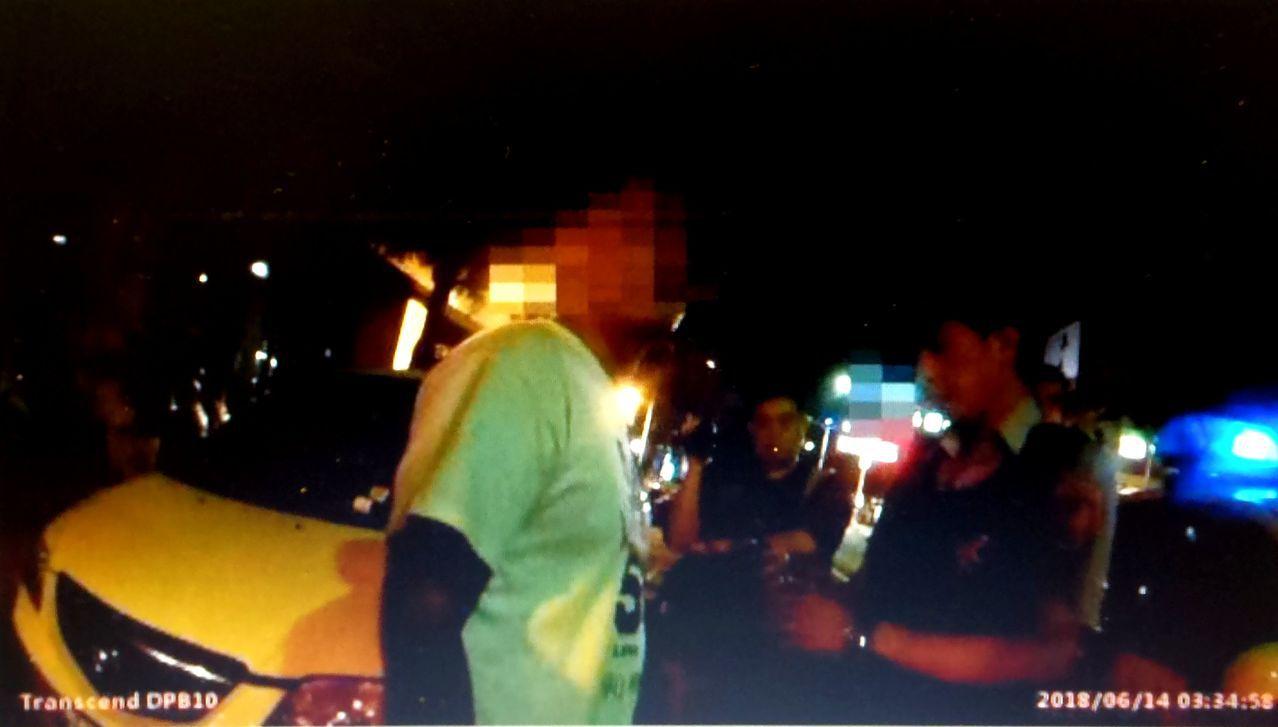 黃姓男子(左)涉嫌酒駕,儘管朋友一再在旁「干擾」,警方仍依法查辦黃。記者林保光/...