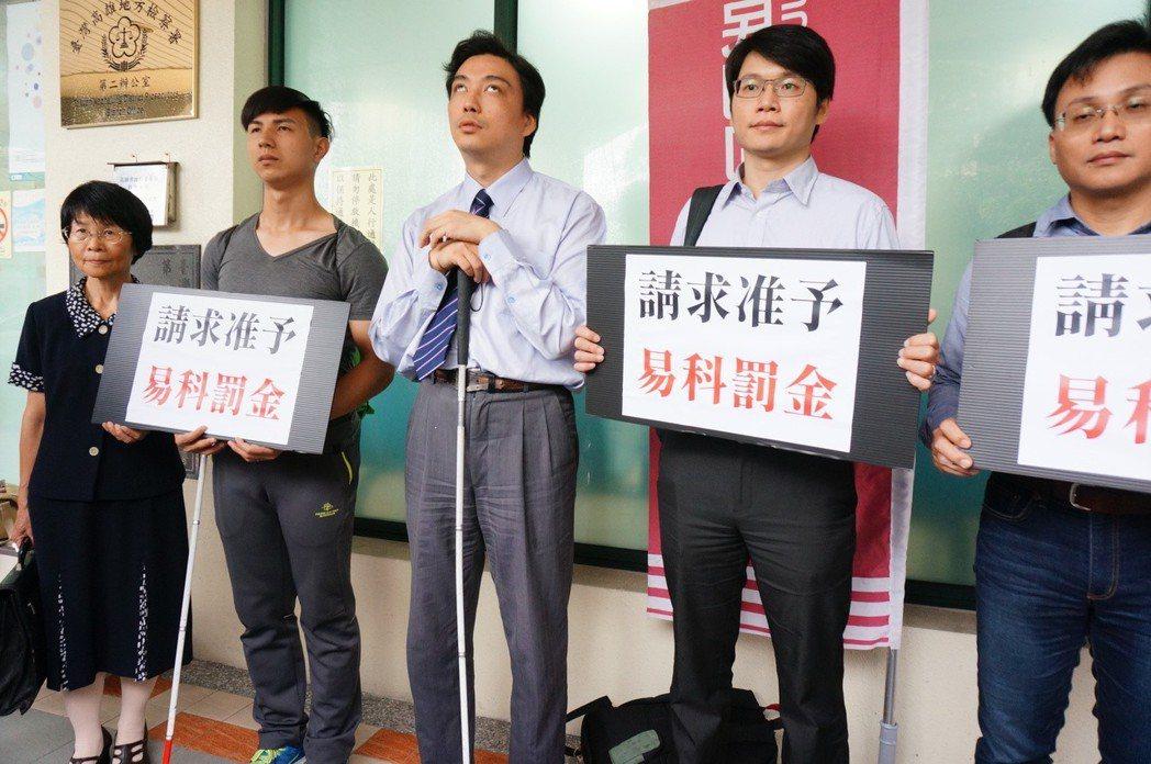 陳敬鎧(左二)今天由民間司改會律師陪同赴雄檢二辦報到。記者林伯驊/攝影