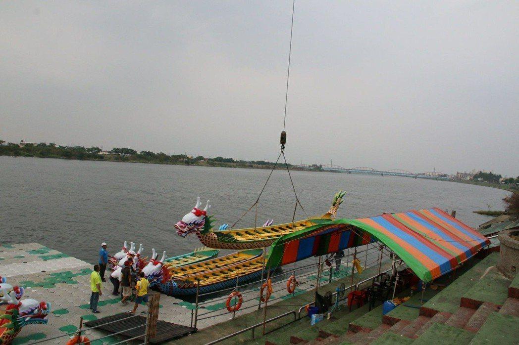 東港鎮公所13日下午將龍舟吊掛上岸安置。圖/公所提供