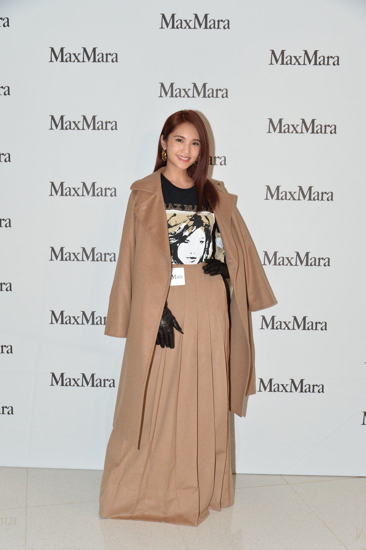 楊丞琳身穿Manuela大衣、印花logo T恤、駝色百褶裙,並搭襯羊皮手套、綁...