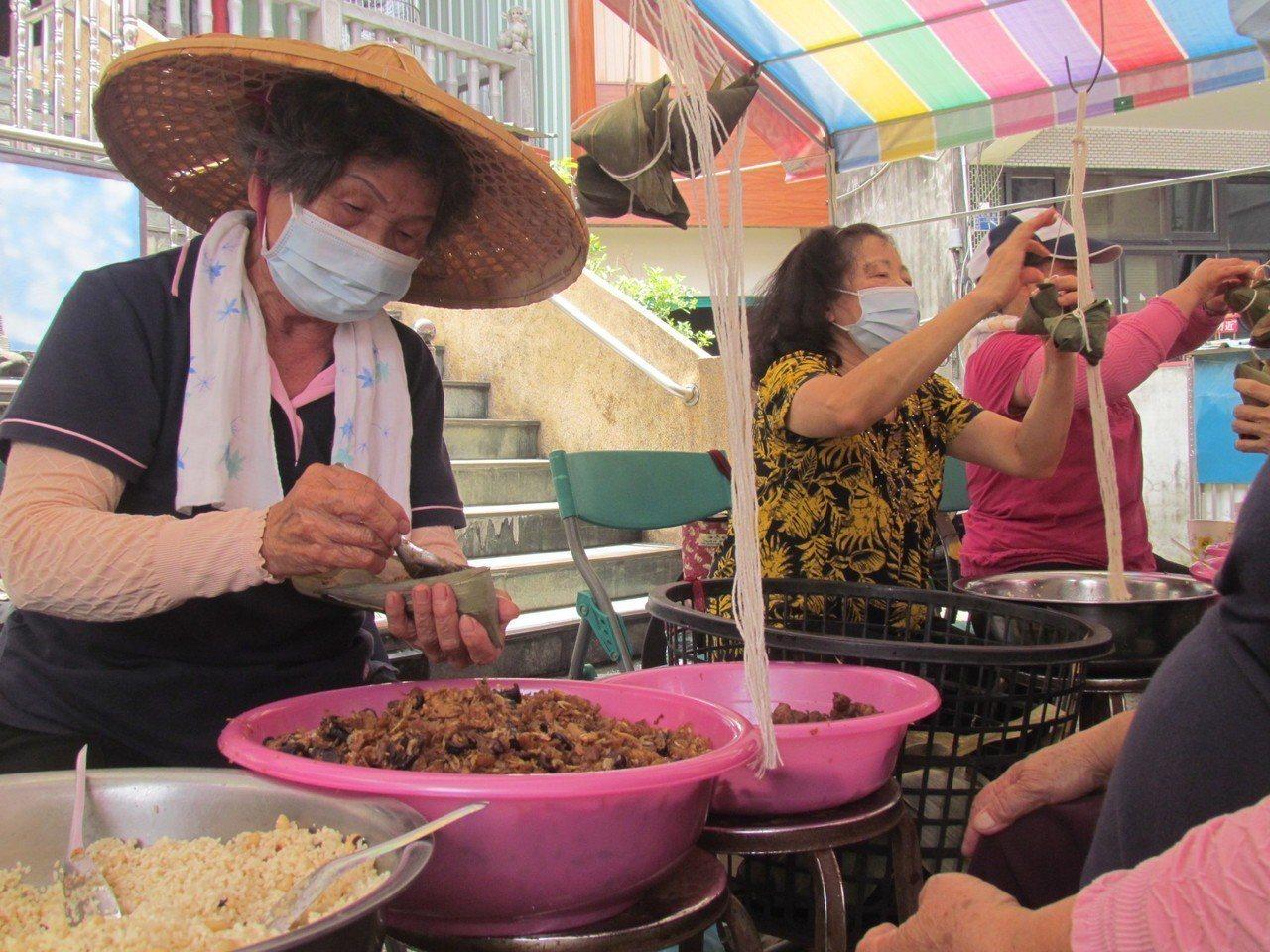 87歲的阿嬤曾設悅每年都來幫忙包粽,她說,能幫弱勢家庭,自己也感到溫暖。記者張家...