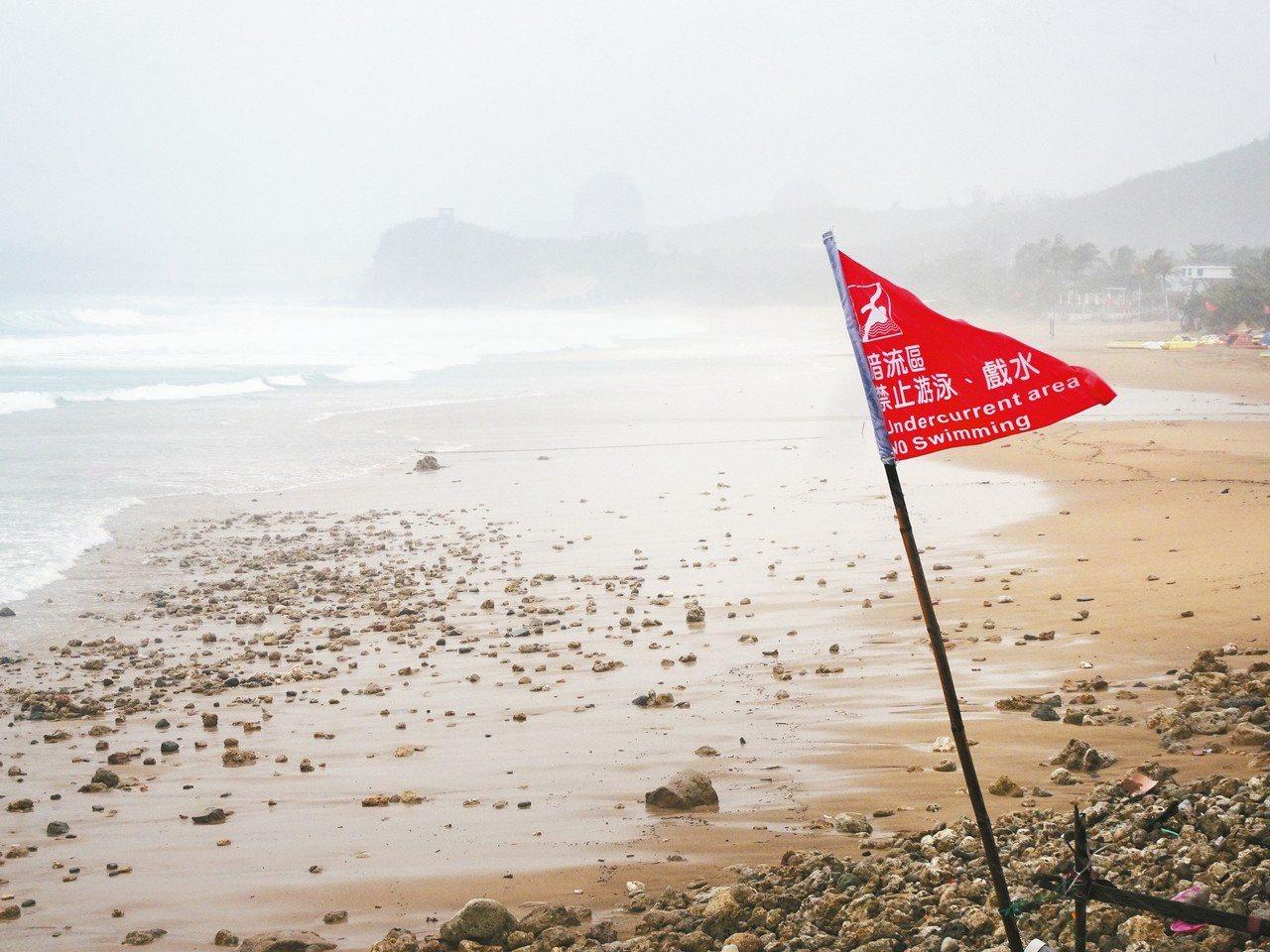 屏東墾丁昨天烏雲蔽日,海岸掀起逾2公尺長浪,岸邊均插上禁止下水的紅旗。 記者潘欣...