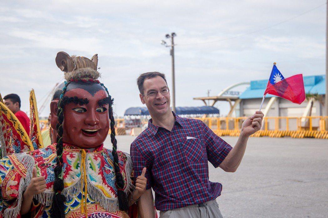 外籍旅客拿著台灣國旗開心與三太子合影。記者蔡翼謙/攝影