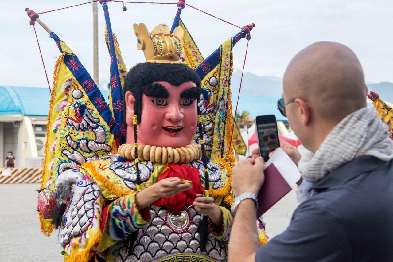外籍旅客對台灣民俗文化電音三太子感到好奇。記者蔡翼謙/攝影