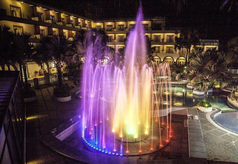 夜晚泳池旁上演璀璨水舞燈光秀。