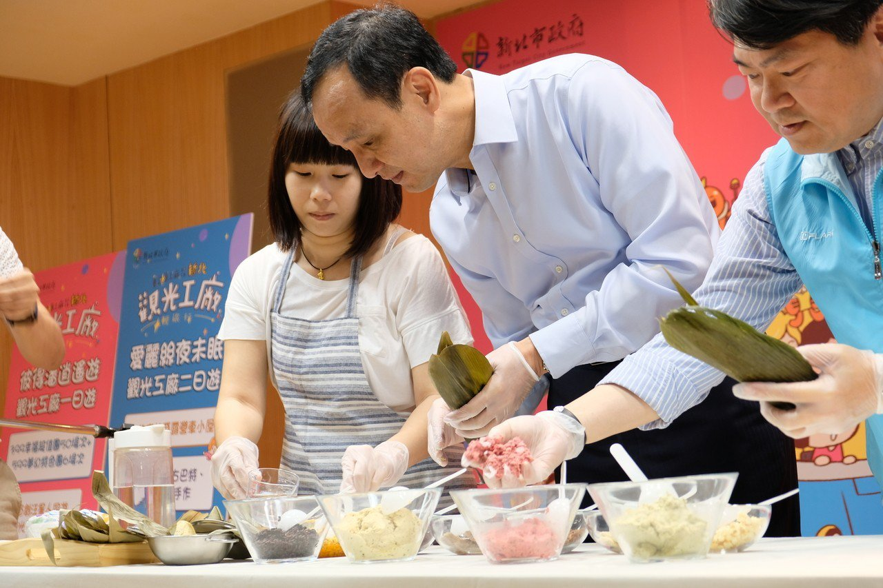 新北市長朱立倫在觀光工廠輕旅行啟動記者會中,製作「肉粽」,所有食材都專為毛小孩挑...