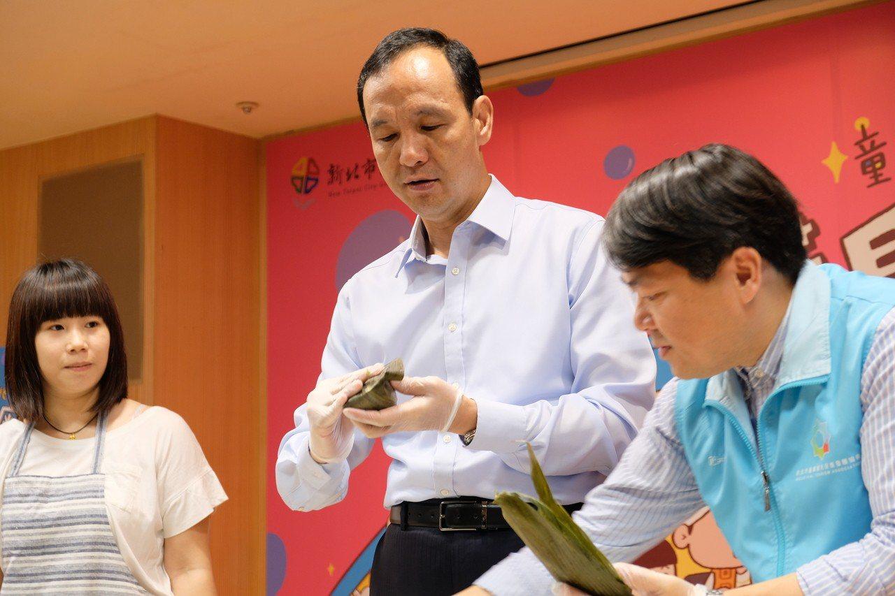 新北市長朱立倫手勢熟練地製作專屬毛小孩的「肉粽」。記者張曼蘋/攝影