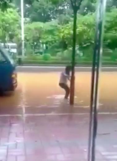 一名路人涉水過馬路時,疑似因觸電倒地。圖/翻攝自微博影片