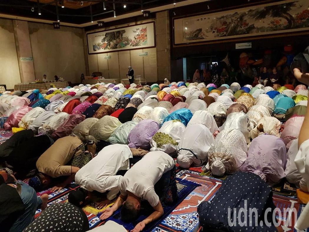 走入開齋儀式現場,基隆市藝文中心地面鋪上印有清真寺圖樣的地毯,印尼籍穆斯林正虔誠...