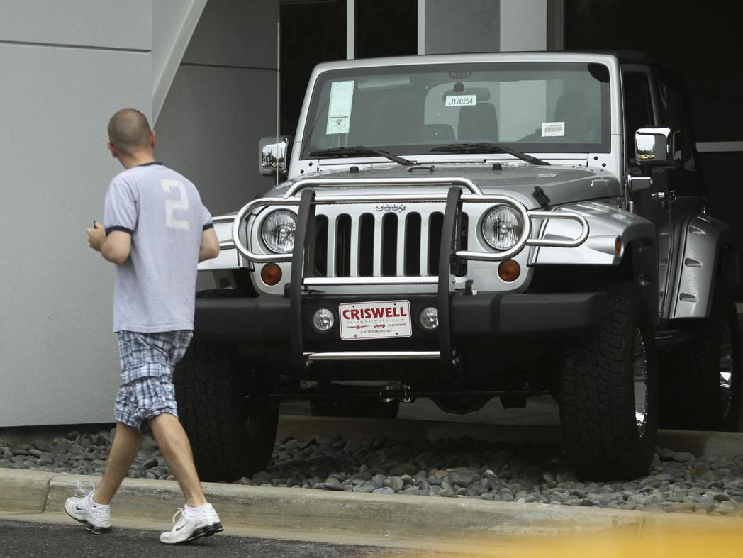一名消費者從Jeep Wrangler車前走過。路透
