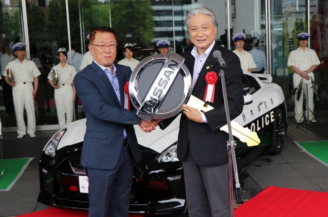 兩方代表以鑰匙交接,象徵Nissan交車給予警方。 摘自carscoops