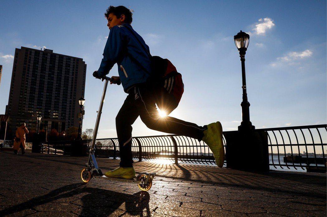 一個男孩清晨在紐約騎著電動滑板車。 (路透)