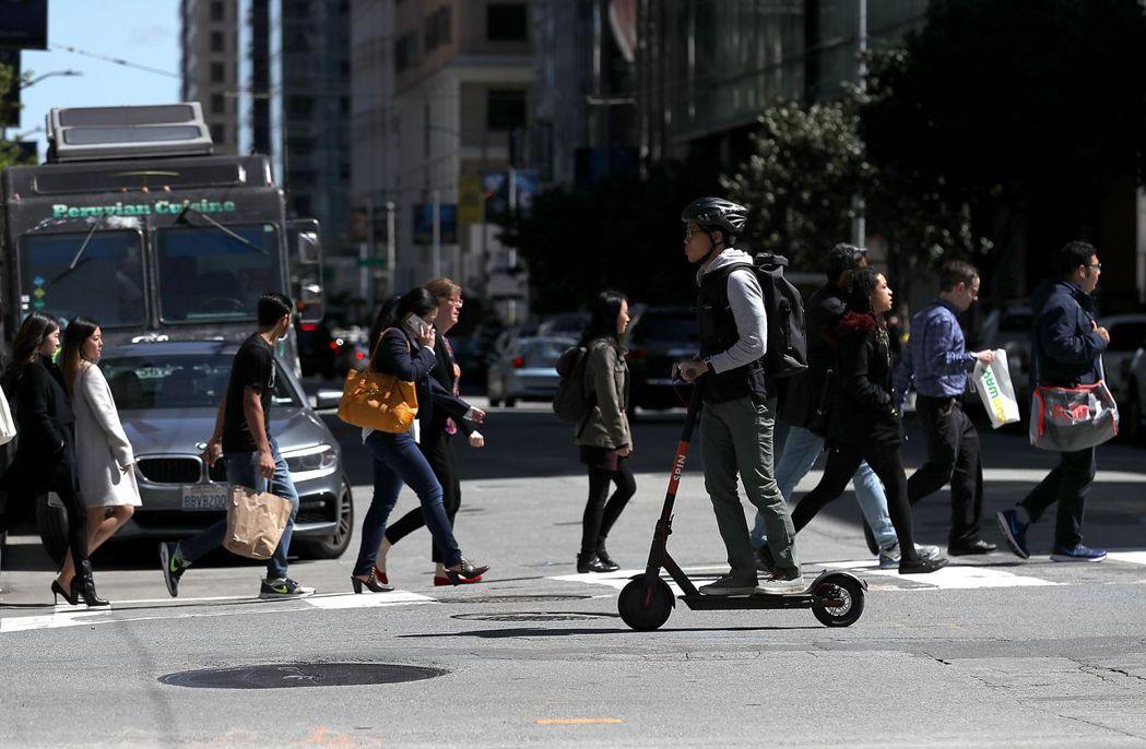 一名男子在美國舊金山市騎著電動滑板車。舊金山打算給每家滑板車公司的滑板車數量定個...