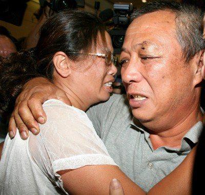 「聯合號」船長何鴻義(右)搭機返台,在機場與太太相擁而泣。 圖/聯合報系資料照片