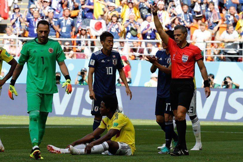 哥倫比亞隊中場桑契斯在開賽沒多就吞下本屆世足賽首張紅牌,他難過地癱坐在地上,同時...