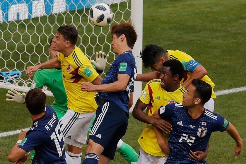 日本隊前鋒大迫勇也(中)在哥倫比亞三位球員接近貼身的防守之下,竟然還能把球頂進,...
