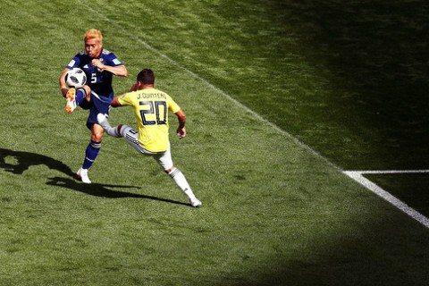 圖為比賽上半場,日本隊的左後衛長友佑都(左),與哥倫比亞攻擊中場奎因特羅(Jua...