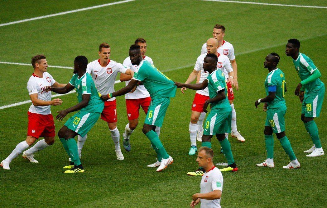 塞內加爾靠著拉著隊友球衣,來阻止波蘭隊搶球。 路透