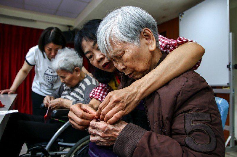 志工手把手細膩地引導長輩一同穿線插針。圖/生命力新聞