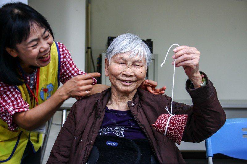 奶奶開心的秀出自己剛剛完成的作品。圖/生命力新聞