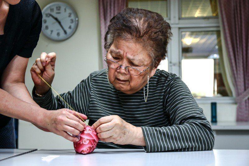 奶奶認真的依照志工引導的步驟拉針線。圖/生命力新聞