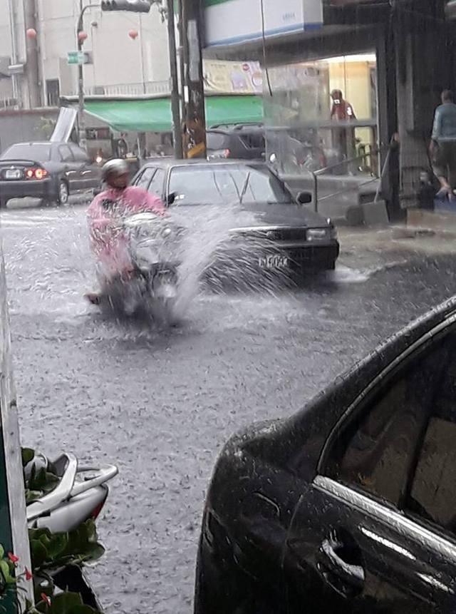 安中路一段701巷路口上午積水,民眾在大雨中騎機車通過積水路段。圖/翻攝畫面