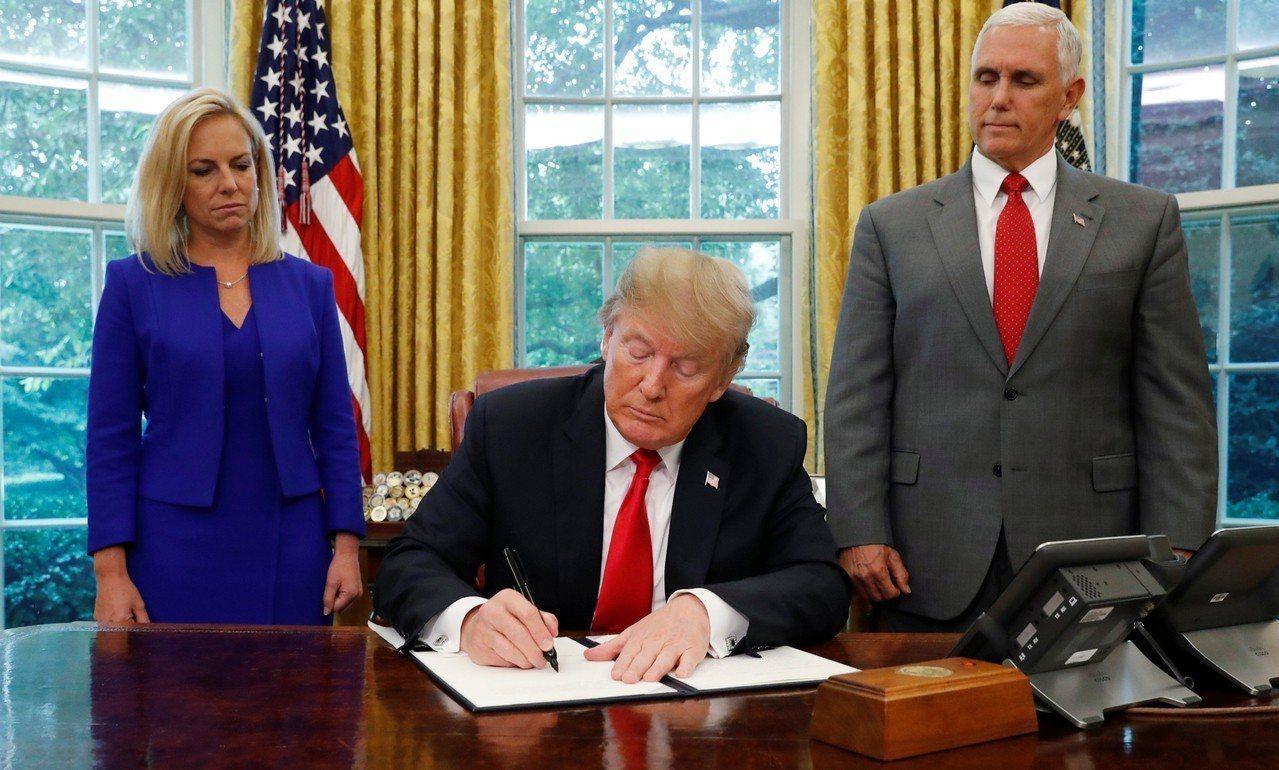 美國總統川普在副總統潘斯(右)與國土安全部長尼爾森(左)陪同下簽署行政令。 路...