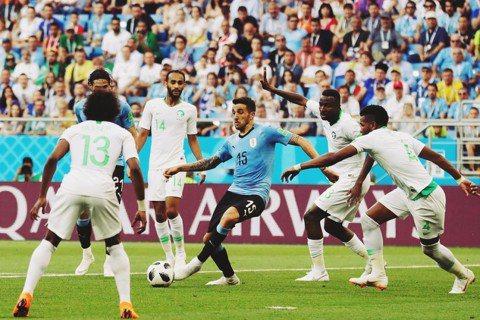 圖為比賽中,烏拉圭中場維西諾(Matías Vecinoy),在前場遭到4名沙烏...