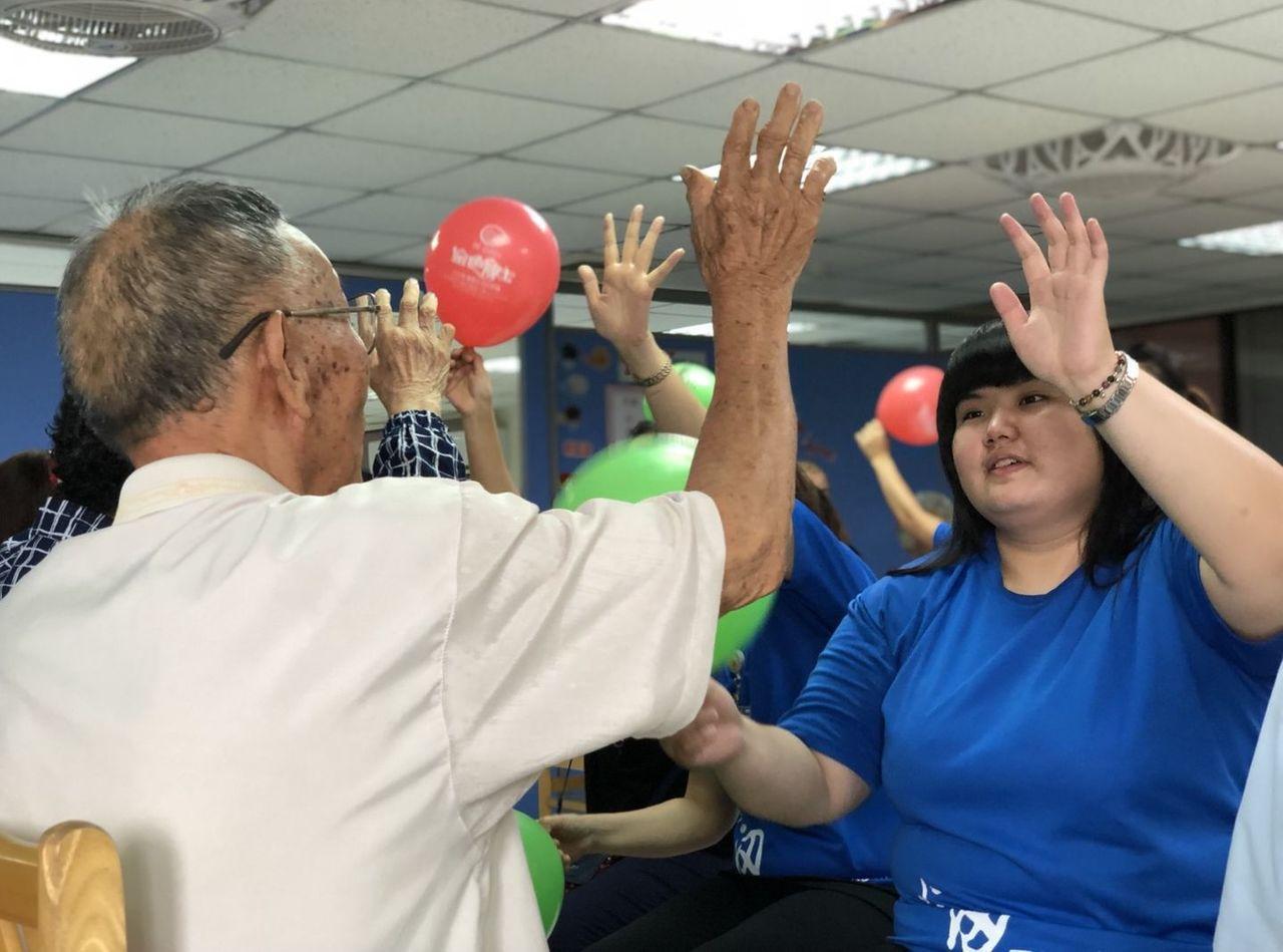 台中市龍井區設置的失智社區服務據點今舉辦班親會,學員與家屬 、照服員一起以氣球和...