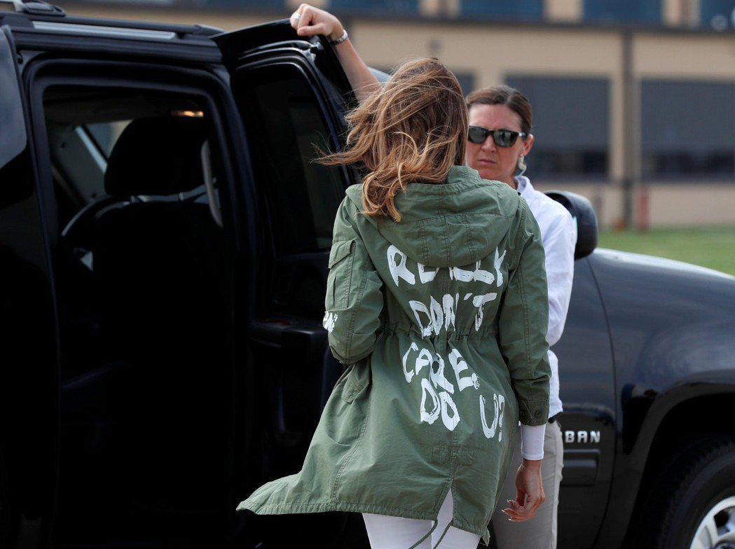 美國第一夫人梅蘭妮亞21日出發前往探訪兒童卻穿印有「我真的不在意」字樣的橄欖綠外...