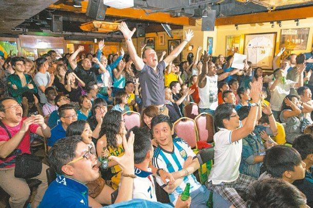 許多球迷凌晨聚集在運動主題酒吧觀看世足賽,圖非當事人。記者鄭清元/攝影