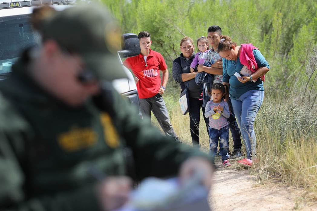 一群中美洲無證移民12日在德州麥卡倫市,等著被美國邊防警衛隊拘禁。法新社