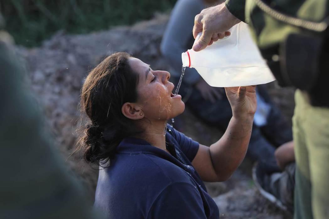 美國邊防警衛隊12日在德州麥卡倫市附近蔗田逮捕一名無證移民後,拿水給她喝。法新社