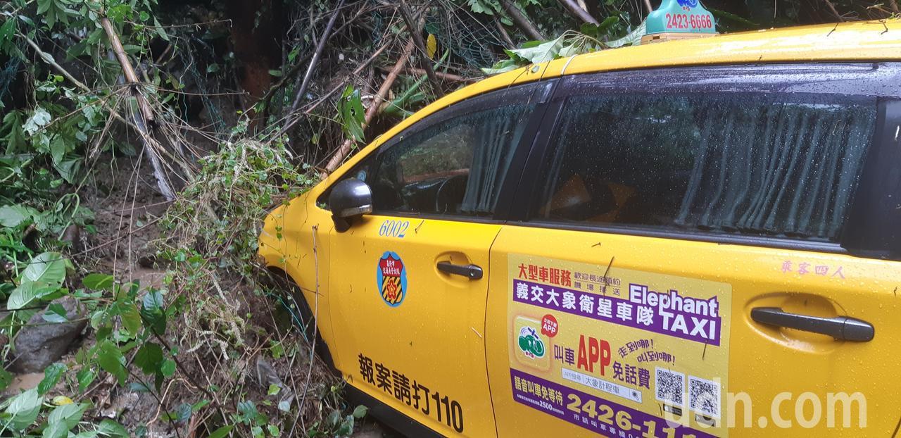 臨停八堵隧道口邊坡下的小黃被滑落路樹壓著。記者賴郁薇/攝影