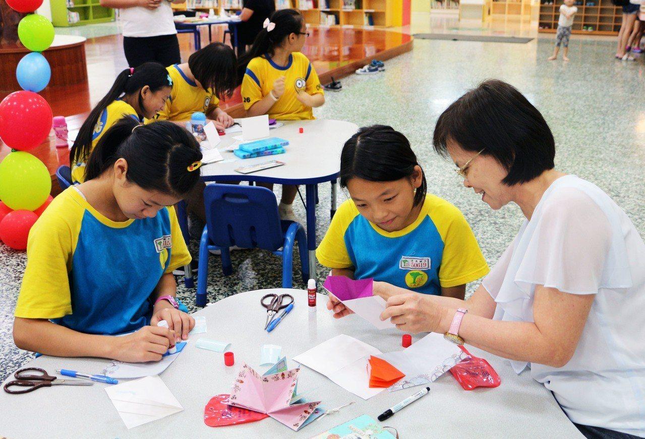 手工書達人王淑芬老師(右)教學童製作屬於自己的創意閱讀手工。圖/新北市立圖書館提...