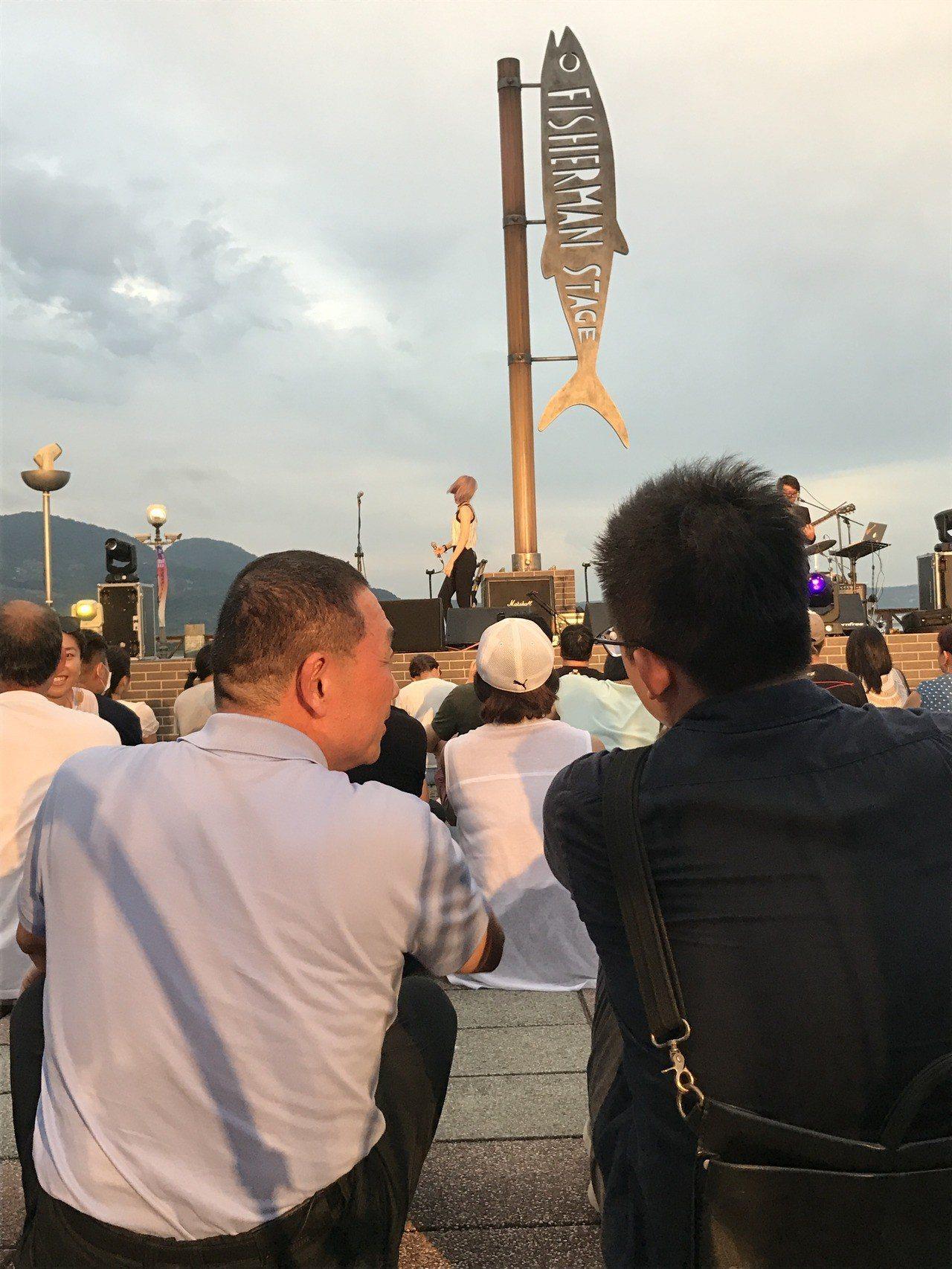 國民黨新北市長參選人侯友宜今晚到淡水漁人碼頭參加原創音樂祭,席地而坐耹聽欣賞。記...