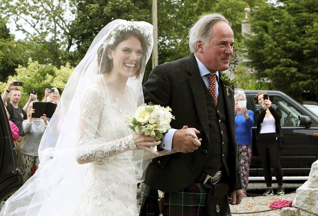 蘿絲李斯利握著父親的手進禮堂。(美聯社)