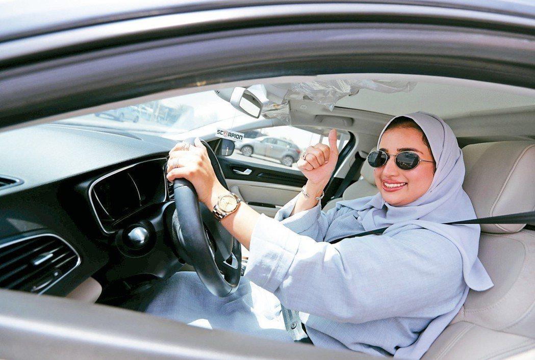 沙烏地阿拉伯廿四日解除女性開車禁令。在達蘭,一名女駕駛對著鏡頭豎起拇指。 (路透...