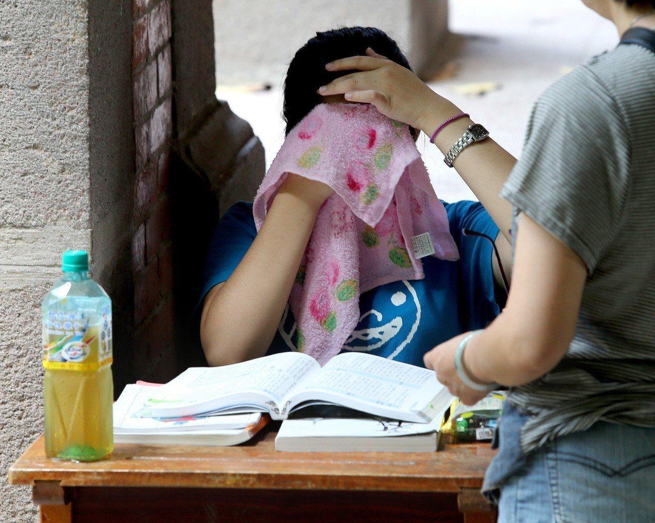 大學指考氣溫炎熱,建中考場內一名考生在走廊上一邊看書,一邊用毛巾擦汗。聯合報系資...