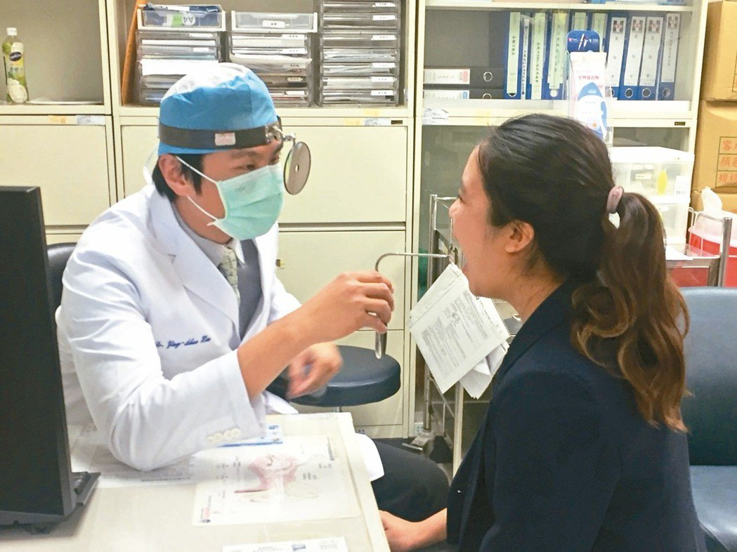 新光醫院耳鼻喉科醫師徐英碩(左)檢查病人喉部。 記者張益華/攝影