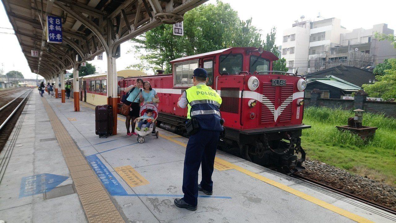 遊客很幸運搭到阿里山火車,請警察先生幫忙拍照留念。記者謝恩得/攝影