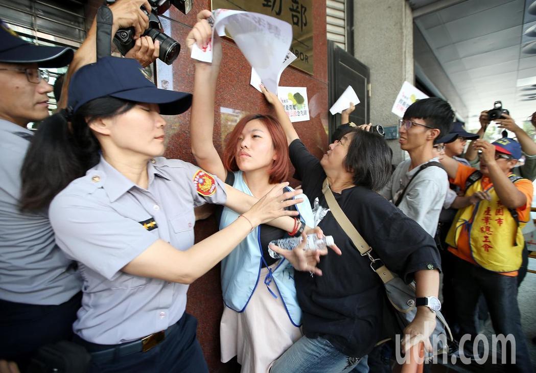 抗議民眾試圖將抗議標語貼上勞動部招牌,與警方爆發多次推擠衝突。記者高彬原/攝影
