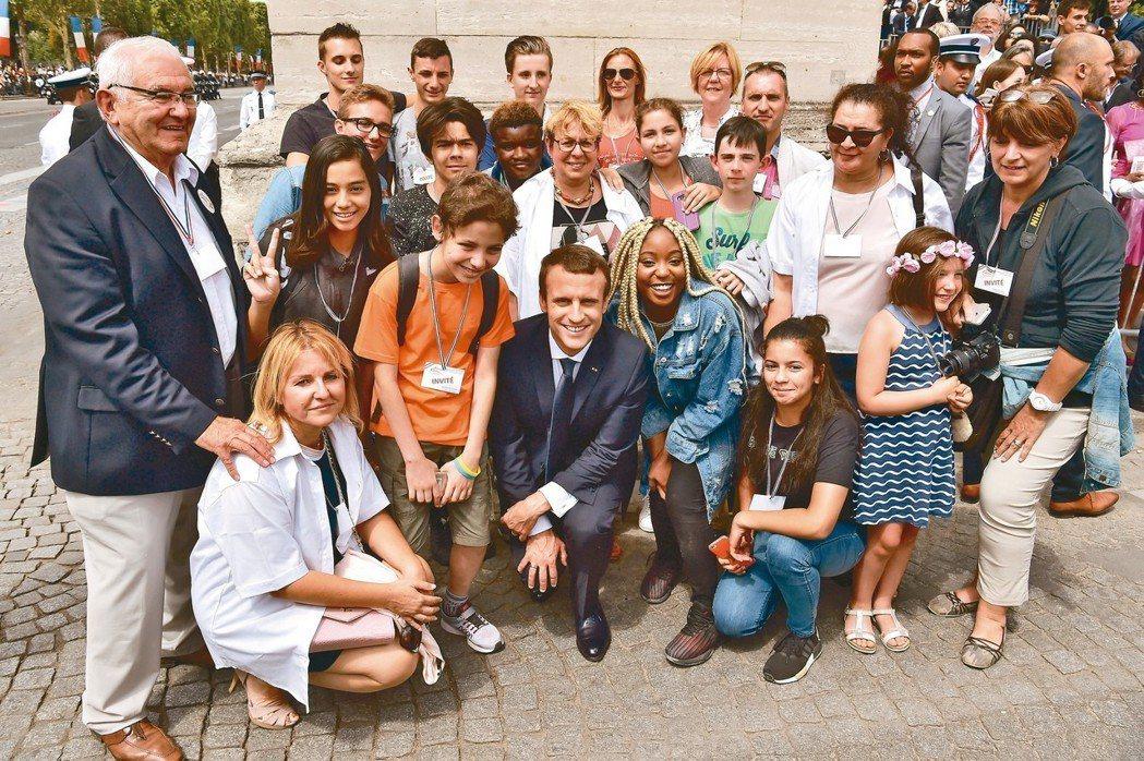 法國總統馬克宏(中)擬推動青少年國家服務,圖為馬克宏在去年7月14日巴士底日與年...