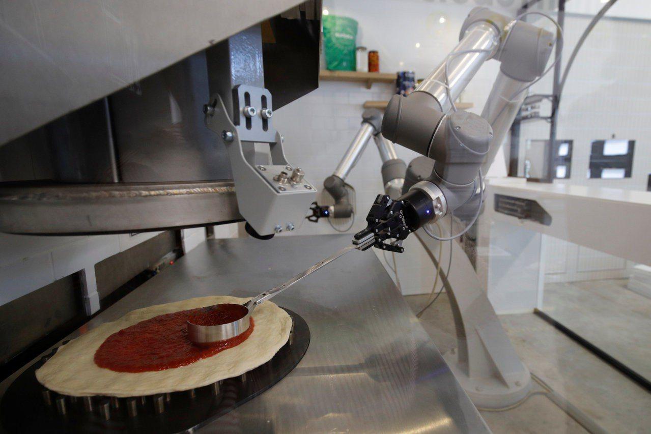 Ekim公司的披薩廚師機器人26日當著消費者的面,演示如何烤出美味披薩。路透