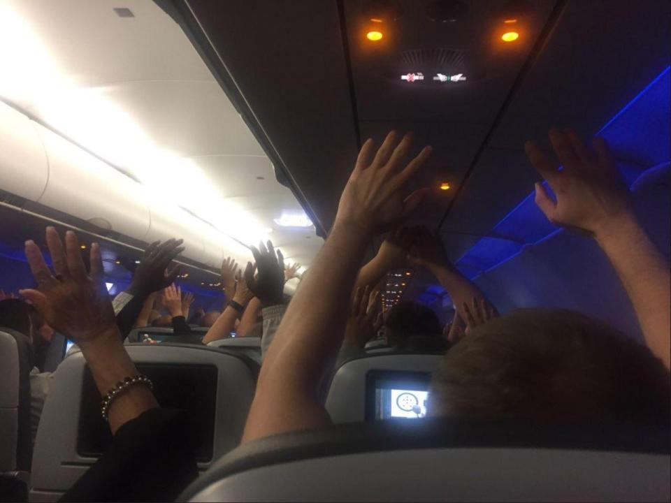 機上乘客被要求高舉雙手,警方進行搜索。圖/取自《太陽報》