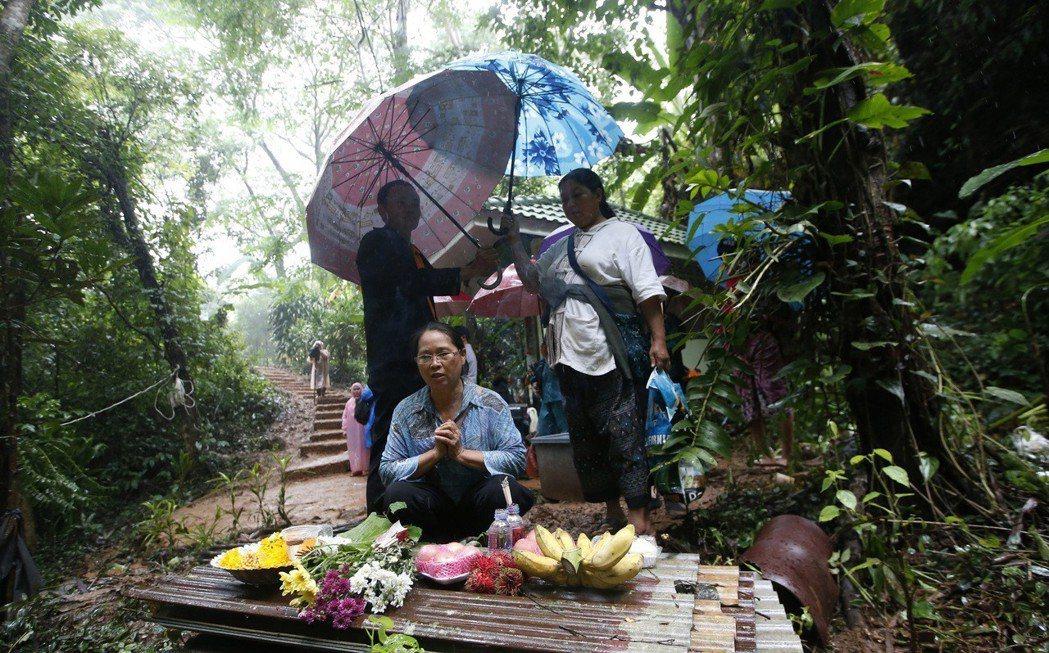 失蹤者家屬在洞外擺出供品,為家人祈求平安脫困。 (美聯社)