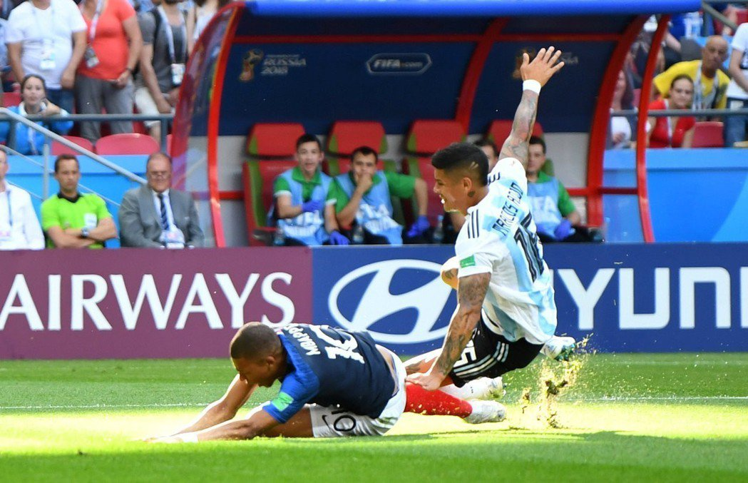 開賽13分鐘,法國姆巴佩(左)被阿根廷球員從後鏟球。 路透