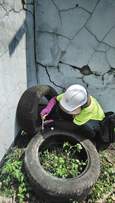稽查人員檢查廢棄輪胎有積水情形。 圖/高雄市衛生局提供