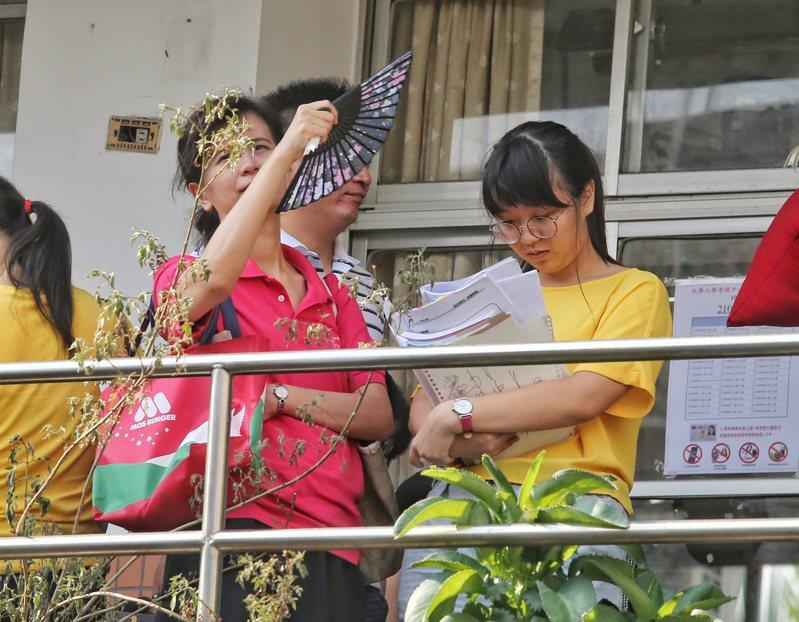 107學年度大學指考昨天進入第一天,物理、化學、生物先登場,北部地區天氣炎熱,有家長在旁搧風替考生消暑。記者鄭清元/攝影