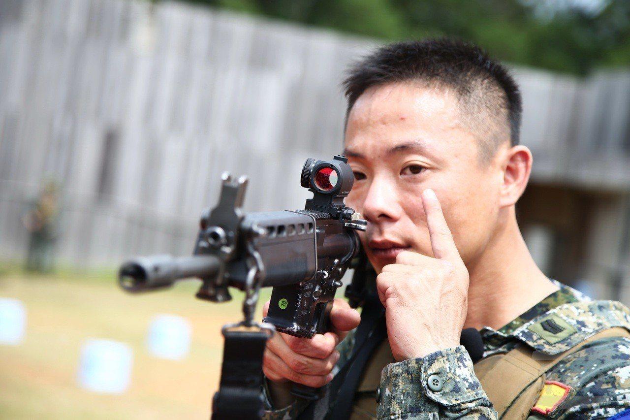 憲訓中心教官王澤雄士官長示範使用內紅點反射式瞄準鏡的射擊姿勢,特徵在於無視差設計...